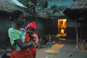 Adivasi_mother_child_before_lighted_house